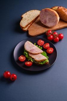 Panino con carne di prosciutto di tacchino, insalata verde e fette di pomodorini freschi sulla piastra nera vicino agli ingredienti sul tagliere, sfondo blu minimo, vista di angolo