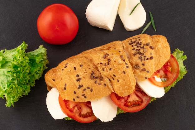 Panino con croissant con mozzarella e pomodoro su pietra nera.