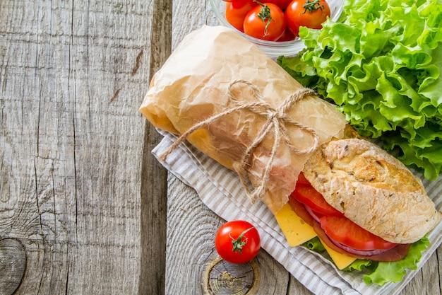 Panino con formaggio e prosciutto, insalata e pomodori