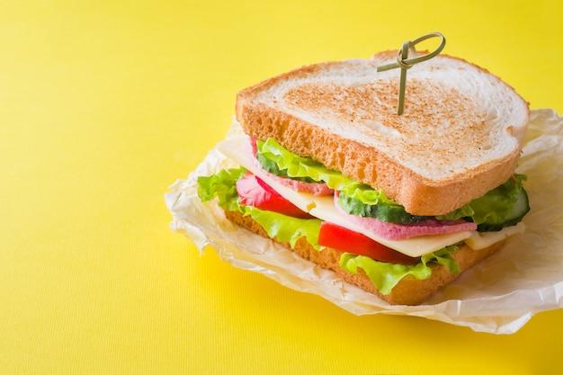 Panino con formaggio, prosciutto e verdure fresche su giallo brillante