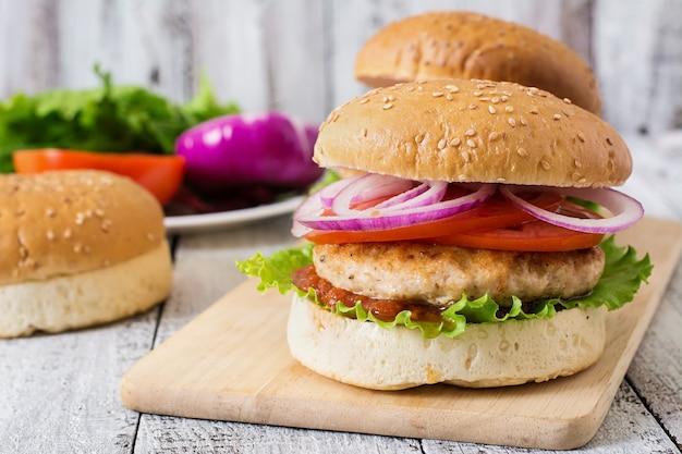 Panino con hamburger di pollo, pomodori, cipolla rossa e lattuga