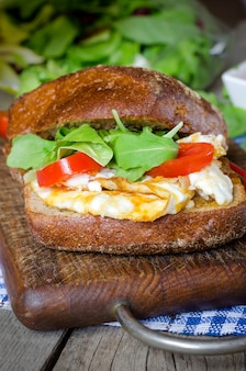 Panino con pane nero, uova e pomodori