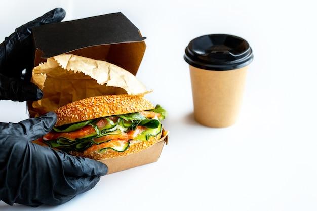 Panino con pesce rosso, formaggio, rucola e avocado.burger con pesce con te alimento da asporto alimento di consegna a domicilio un panino è imballato con caffè.caffè e asporto le mani ricoperte prendono il cibo.