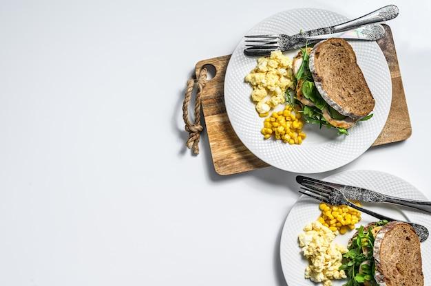 Panino con petto di pollo, rucola, frittata e mais. vista dall'alto. copia spazio