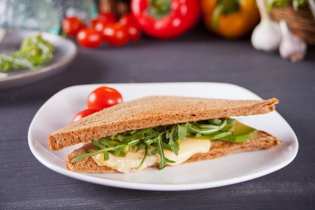 Panino con petto di tacchino, formaggio, lattuga, rucola, pomodori e cipolla su un piatto nero