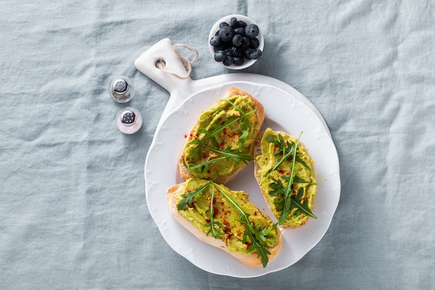 Panino con rucola e avocado con paprika sul tavolo. colazione sana o spuntino su un piatto su una tovaglia di lino blu