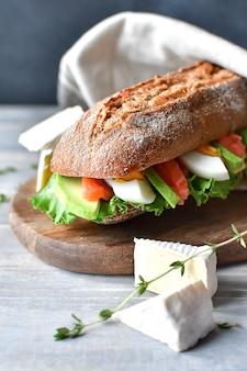 Panino con salame e formaggio su un piatto di legno