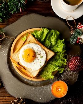 Panino con uovo servito con lattuga
