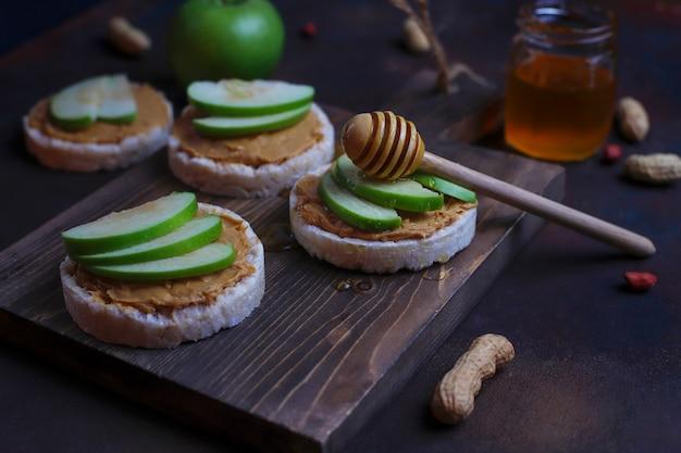 Panino croccante al burro di arachidi naturale con pane di torta di riso e fette di mela verde e miele.