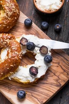 Panino dei bagel con formaggio cremoso e sul mirtillo sulla tavola di legno