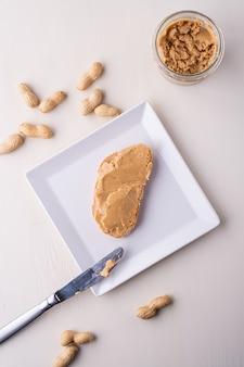 Panino del pane di burro di arachidi sul piatto a forma di quadrato bianco