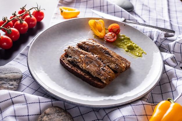 Panino di aringhe affumicato casalingo con pane di segale sul piatto grigio chiaro, vista superiore