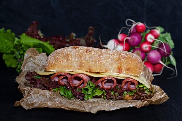 Panino di ciabatta croccante con prosciutto, formaggio e foglie di lattuga.