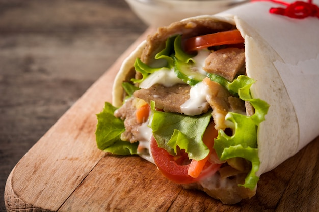 Panino di doner kebab o shawarma sulla tavola di legno.