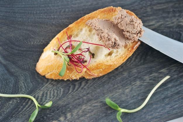 Panino di pane tostato bruciato con patè ed erbe su una tavola di legno scura