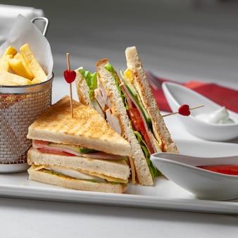 Panino di vista laterale sulla tavola con le patate fritte, ketchup su fondo bianco.