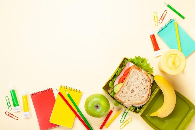 Panino e mela freschi per il pranzo sano nella scatola di pranzo di plastica