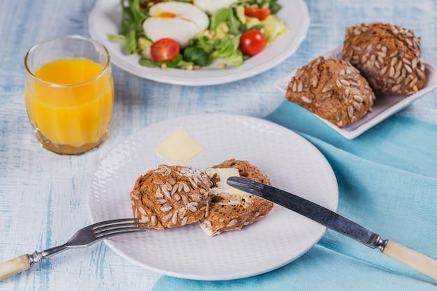 Panino e uovo in camicia con insalata verde, pomodori, pane integrale e succo d'arancia su legno.