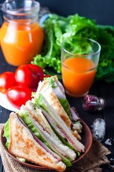 Panino fatto in casa con insalata e succo come sana colazione