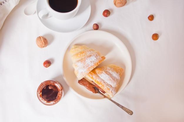 Panino fresco dei croissant con cioccolato sul piatto, tazza di caffè sui precedenti bianchi