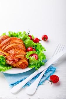 Panino fresco del croissant con il prosciutto spuntino estivo