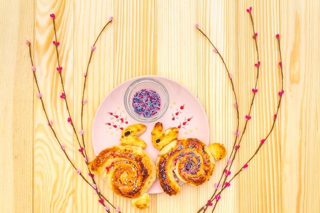 Panino fresco sotto forma di un coniglietto di pasqua. il concetto di cibo per le vacanze dei bambini. nel piatto in ceramica rosa con rami di salice artificiale su superficie di legno, vista dall'alto, da vicino.