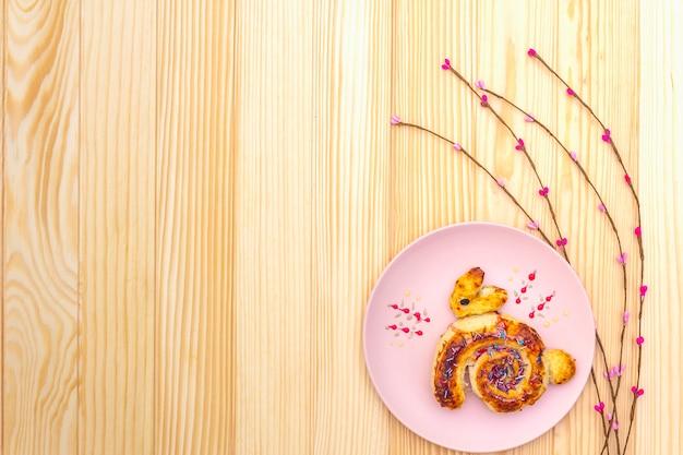 Panino fresco sotto forma di un coniglietto di pasqua. il concetto di panetteria per le vacanze dei bambini. nel piatto in ceramica rosa con rami di salice artificiale su superficie di legno, copia spazio, vista dall'alto.