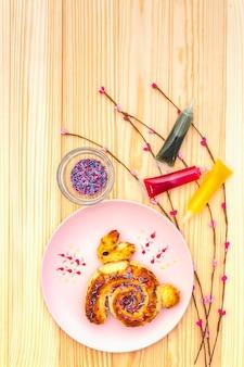 Panino fresco sotto forma di un coniglietto di pasqua. il concetto di panetteria per le vacanze dei bambini. nel piatto in ceramica rosa con rami di salice artificiale su superficie di legno, vista dall'alto, da vicino.