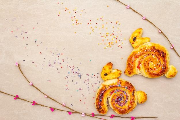 Panino fresco sotto forma di un coniglietto di pasqua. il concetto di panetteria per le vacanze dei bambini. sulla superficie di pietra con rami di salice artificiale, copia spazio, vista dall'alto.