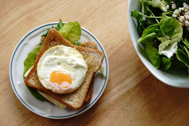 Panino integrale con uova, verdure fresche, prosciutto e formaggio, colazione sana per un nuovo giorno felice e salutare.