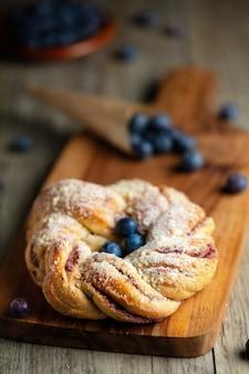 Panino pieghettato mirtillo con zucchero a velo e bacche fresche sul bordo di legno. composizione verticale.