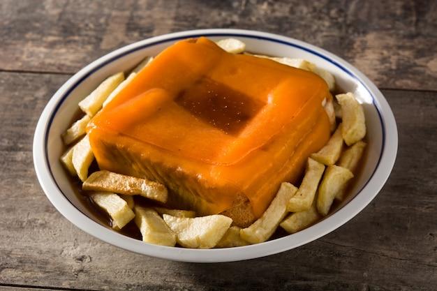 Panino portoghese tipico di francesinha con le patate fritte sulla tavola di legno