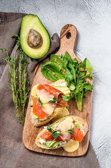 Panino sano con avocado e salmone. insalata di spinaci e rucola. sfondo bianco. vista dall'alto