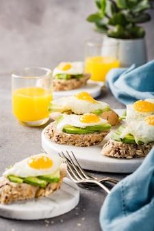 Panino sano con avocado fresco e uova di quaglia fritte