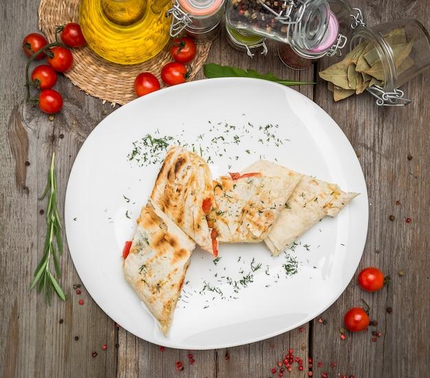Panino shawarma con verdure fresche e salsa sul piatto grigio decotated con pomodorini, foglie di basilico sul tavolo grigio