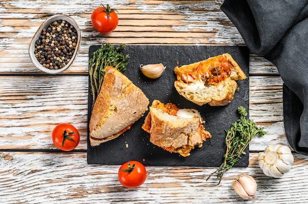 Panino sottomarino vegetariano delle baguette con melanzana arrostita, pepe e feta sulla tavola bianca.