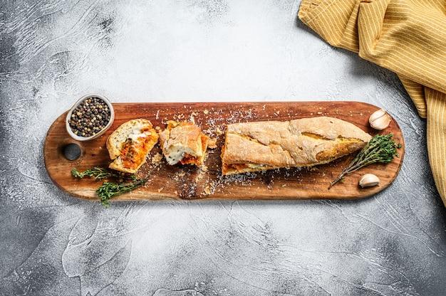 Panino sottomarino vegetariano delle baguette con melanzana arrostita, pepe e feta sulla tavola grigia.