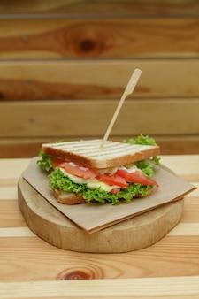 Panino succoso con bacon, verdure fresche, insalata verde e linee scure dopo la griglia sul piatto di legno