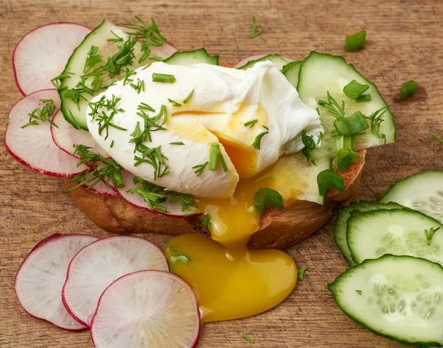 Panino sulla fetta di pane bianco tostato con uova in camicia, foglie verdi di cipolla, colazione del mattino