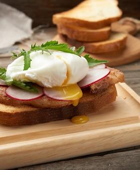Panino sulla fetta di pane bianco tostato con uova in camicia, foglie verdi di rucola e ravanello