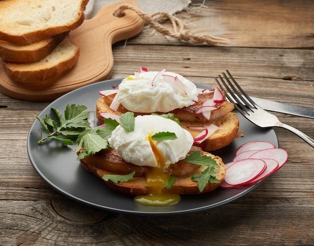 Panino sulla fetta di pane bianco tostato con uova in camicia, gree