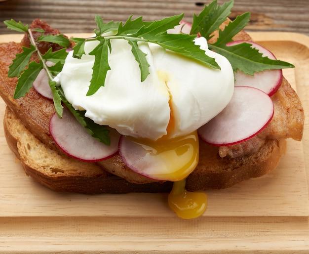 Panino sulla fetta di pane bianco tostato con uova in camicia