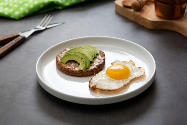 Panino tostato avocado e un uovo fritto su un piatto bianco con asparagi. cibo o colazione sani. sfondo scuro