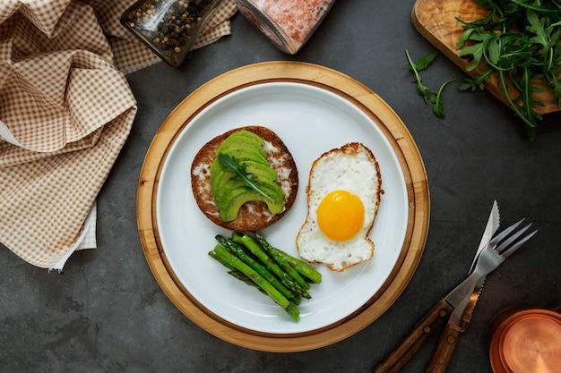 Panino tostato avocado e un uovo fritto su un piatto bianco con asparagi. cibo o colazione sani.