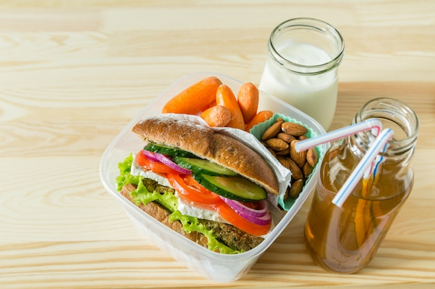 Panino vegano in scatola di pranzo con carote e noci