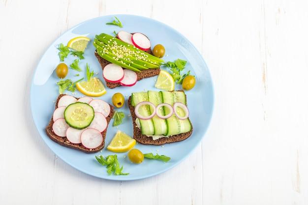 Panino vegetariano aperto di superfood con diversi condimenti: avocado, cetriolo, ravanello sul piatto blu su sfondo bianco. mangiare sano.