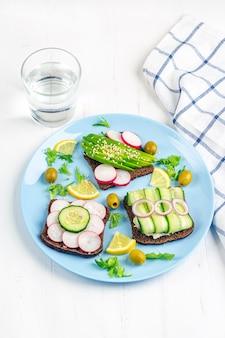 Panino vegetariano aperto di superfood con diversi condimenti: avocado, cetriolo, ravanello sul piatto e bicchiere d'acqua su fondo bianco. mangiare sano. alimenti biologici e vegetariani