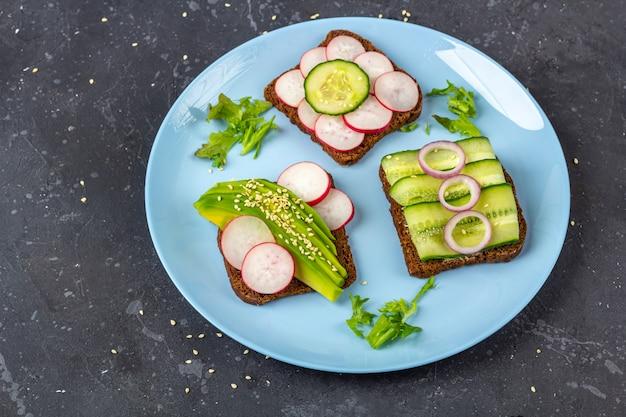 Panino vegetariano aperto superfood con diversi condimenti: avocado, cetriolo, ravanello su piastra su sfondo scuro. mangiare sano. alimenti biologici e vegetariani