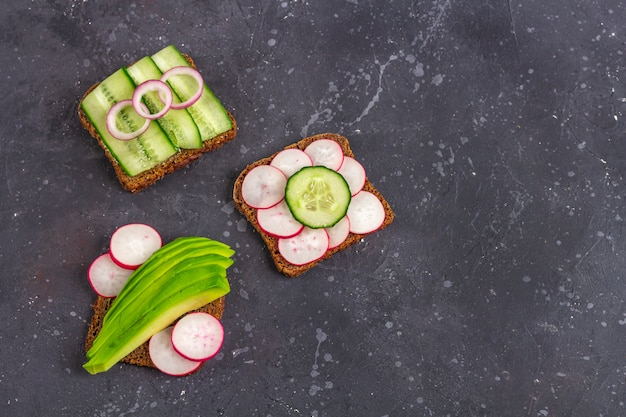 Panino vegetariano aperto superfood con diversi condimenti: avocado, cetriolo, ravanello su sfondo scuro. mangiare sano. alimenti biologici e vegetariani, minimalismo