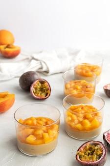 Panna cotta al caramello, budino di crema pasticcera con pesca e frutto della passione, tavolo bianco, spazio di copia